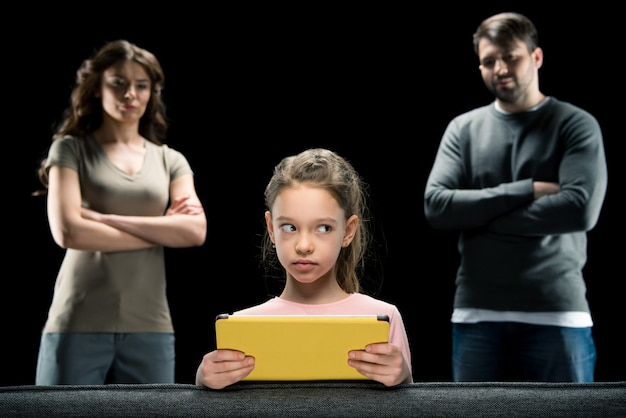 Menina, usando, tablete digital, enquanto, pais, ficar, com, braços cruzados, ligado, pretas