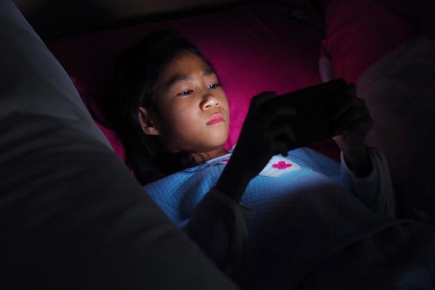 Menina, usando, telefone móvel, ligado, cama escura, em, a, quarto