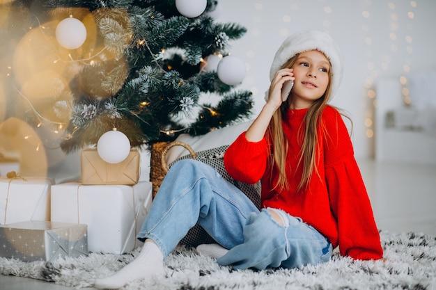 Menina usando telefone perto da árvore de natal no natal