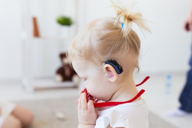 Menina usando um aparelho auditivo.