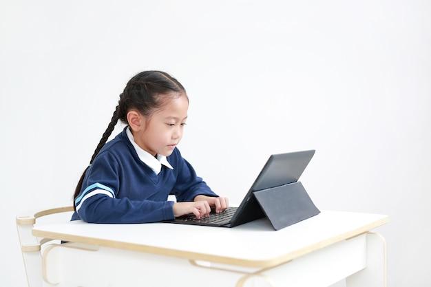 Menina usando um laptop na escola