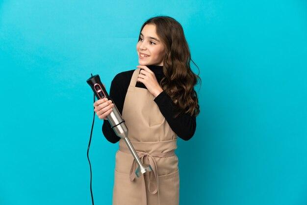 Menina usando um liquidificador isolado na parede azul, olhando para cima enquanto sorri
