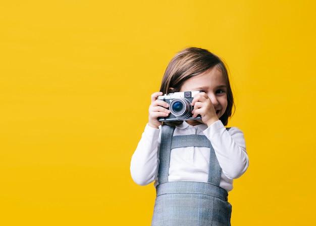 Menina usando uma câmera fotográfica na parede amarela