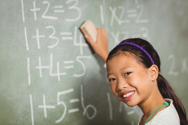 Menina usando uma esponja para quadro-negro