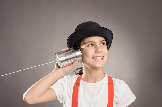Menina usando uma lata como telefone em cinza