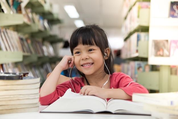 Menina usou o conjunto de audição para ouvir, ela lê um livro na biblioteca