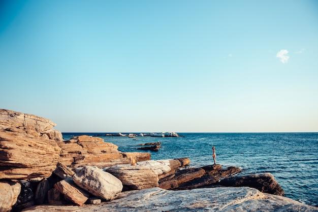 Menina vagando na praia rochosa
