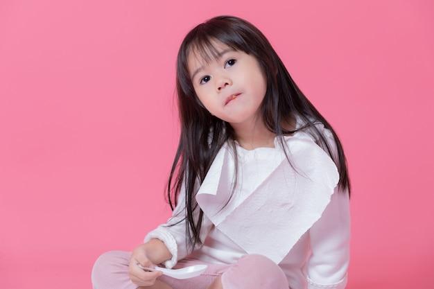Menina vai comer comida por colher de plástico com um lenço de papel feito em um avental na parede rosa.