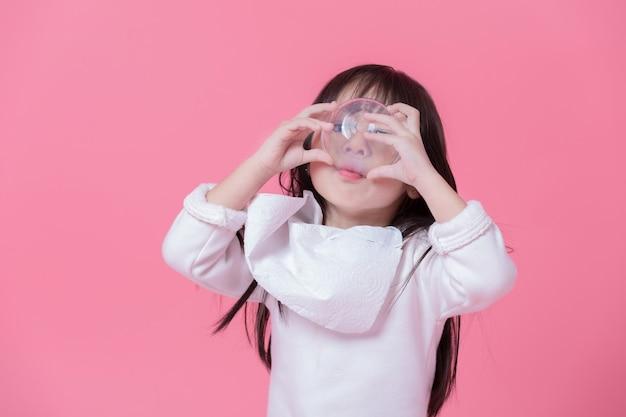 Menina vai comer comida por grande golpe com um lenço de papel feito em um avental na parede rosa.