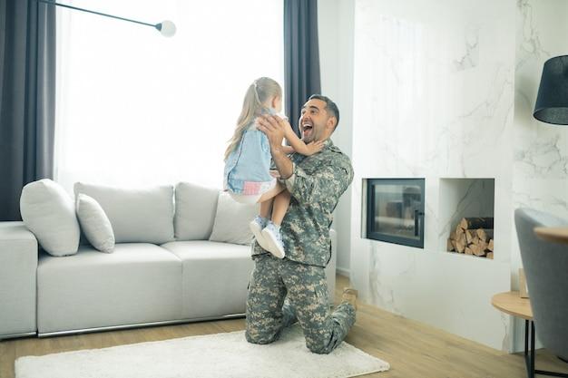 Menina vendo o pai. garotinha loira correndo para o pai vendo-o na sala de estar