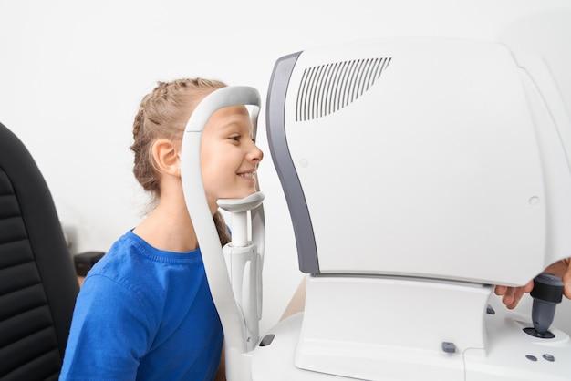 Menina, verificando a visão do olho com equipamento oftalmológico