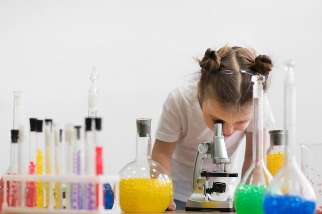 Menina, verificando o microscópio no laboratório