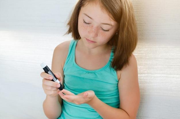 Menina verificando o nível de açúcar no sangue usando lancelete e glicosímetro em casa
