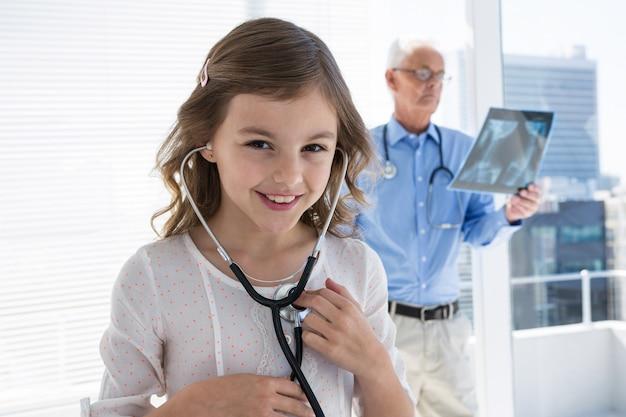 Menina verificando seu próprio batimento cardíaco usando um estetoscópio