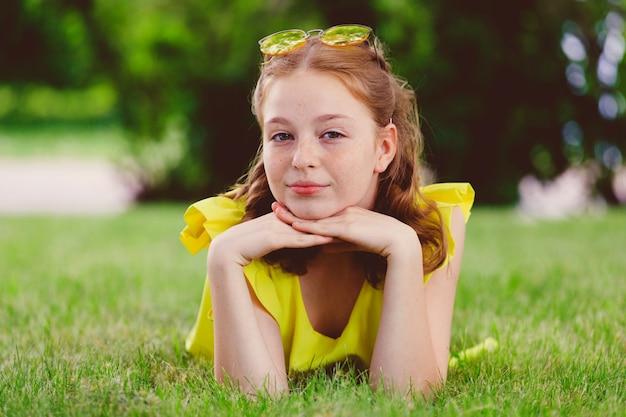 Menina vermelha em um vestido amarelo encontra-se na grama do parque. foto de alta qualidade