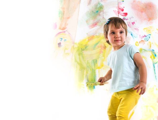 Menina vestida com camiseta azul e calça amarela, segura o pincel nas mãos e desenha