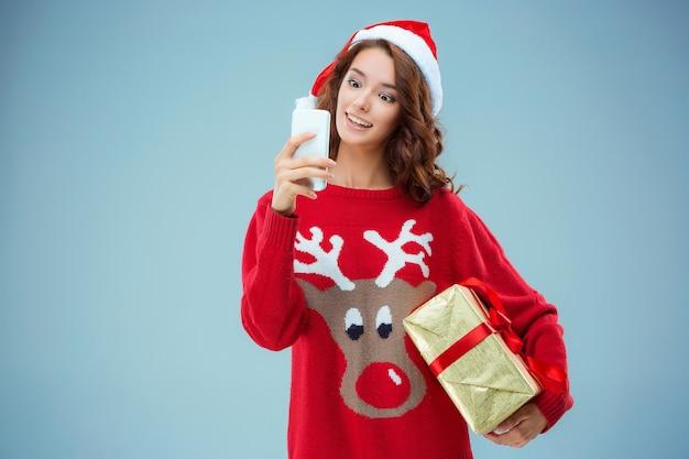 Menina vestida com chapéu de papai noel com um presente de natal e telefone