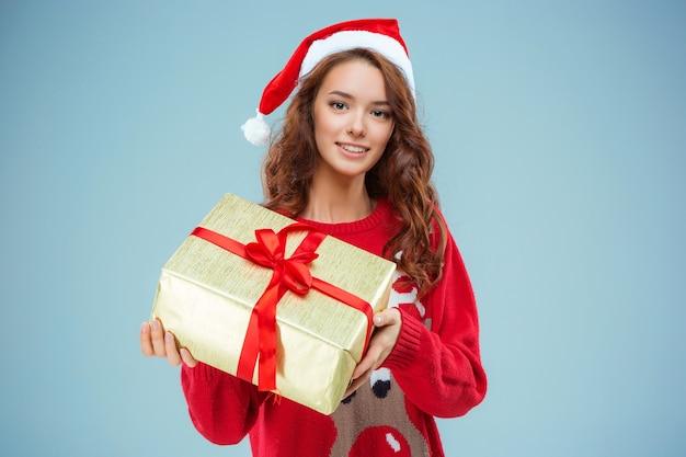 Menina vestida com chapéu de papai noel com um presente de natal