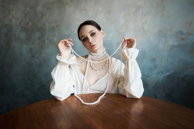 Menina vestida com roupas brancas boho com pérolas brancas em volta do pescoço está sentado em uma mesa.