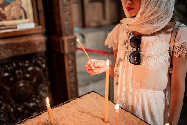 Menina vestida com um cachecol segura uma vela na igreja