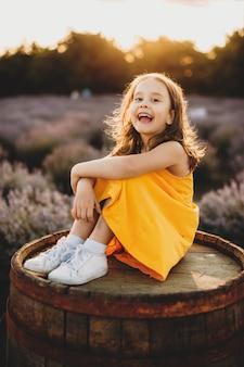 Menina vestida com um vestido amarelo sorrindo feliz enquanto está sentada em um barril contra um campo de lavanda