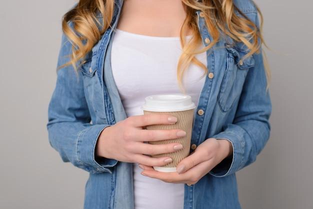 Menina vestida com uma camiseta branca e uma camisa jeans isolada em um fundo cinza segurando uma xícara de café para viagem