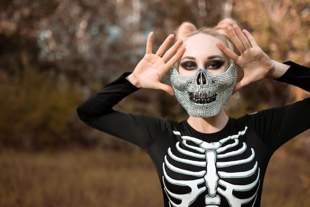 Menina vestida como um esqueleto na floresta de outono. retrato. fechar-se. dia das bruxas