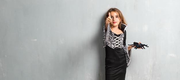 Menina vestida como um vampiro para as férias de halloween com o polegar para cima