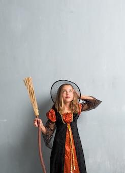 Menina vestida como uma bruxa e segurando uma vassoura para as férias do dia das bruxas e olhando para cima