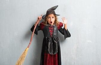 Menina vestida como uma bruxa para as férias de halloween fazendo gesto de surpresa