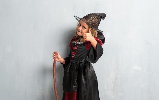 Menina vestida como uma bruxa para as férias do dia das bruxas e com o polegar para cima