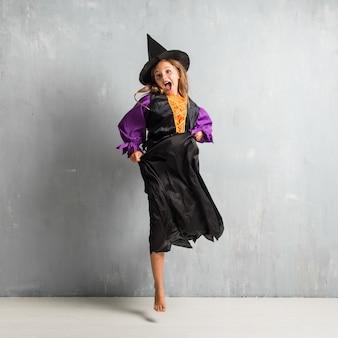 Menina vestida como uma bruxa para as férias do dia das bruxas e pulando
