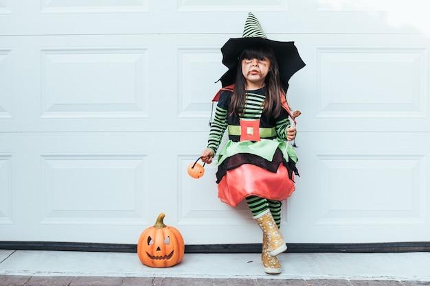 Menina vestida de bruxa comendo doces comemorando o halloween na porta da garagem ao lado de jack o lantern