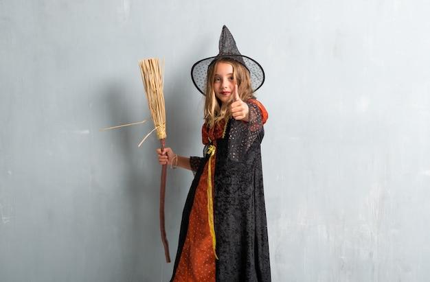 Menina vestida de bruxa e segurando uma vassoura para as férias de halloween com o polegar para cima