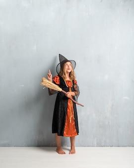 Menina vestida de bruxa e segurando uma vassoura para as férias do dia das bruxas e apontando para cima