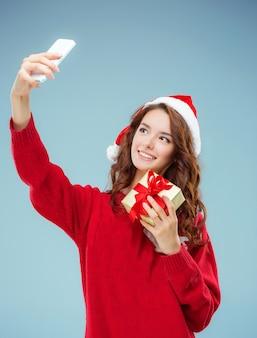 Menina vestida de chapéu de papai noel com um presente de natal e telefone.