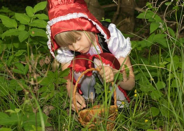Menina vestida de chapeuzinho vermelho na floresta de primavera