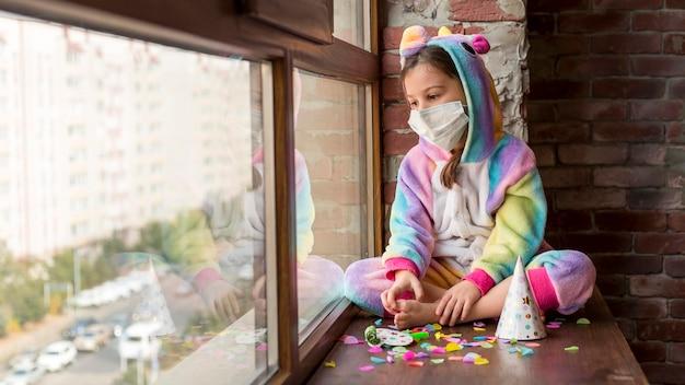 Menina vestida de dinossauro em casa com máscara facial