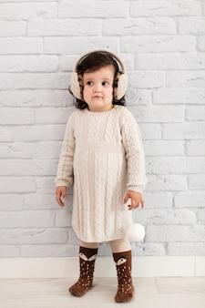 Menina vestida de inverno, olhando para longe