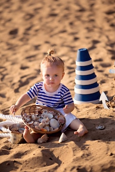 Menina vestida de marinheiro em uma praia com conchas à beira-mar