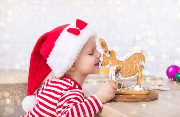 Menina vestida de natal com presentes perto da árvore de natal bebe leite e decora um cervo