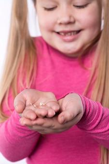 Menina vestida de rosa com um dente de leite caído nas mãos