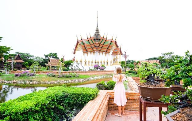 Menina vestida em frente ao salão do trono dusit maha prasat em thaliand