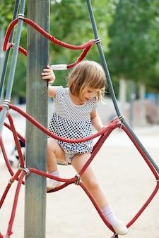 Menina vestida escalando em cordas