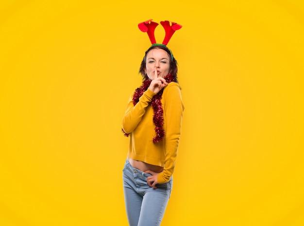 Menina vestida para as férias de natal fazendo gesto de silêncio sobre fundo amarelo