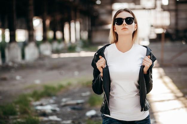 Menina vestindo camiseta, óculos e jaqueta de couro posando contra a rua