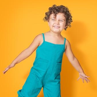 Menina vestindo macacão azul-petróleo sem mangas