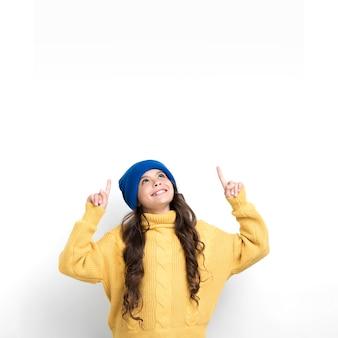 Menina vestindo roupas sazonais e apontando