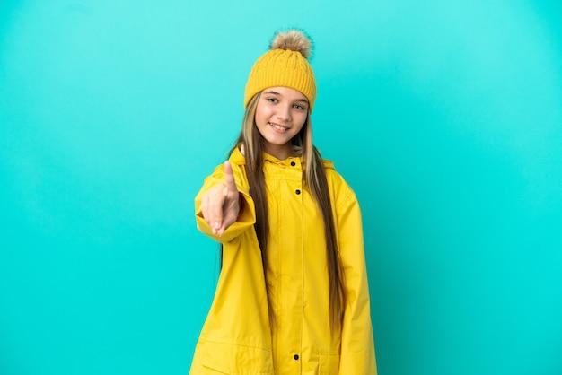Menina vestindo um casaco à prova de chuva sobre fundo azul isolado, mostrando e levantando um dedo