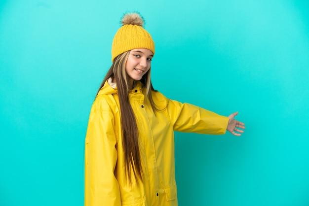 Menina vestindo um casaco à prova de chuva sobre um fundo azul isolado estendendo as mãos para o lado para convidar para vir